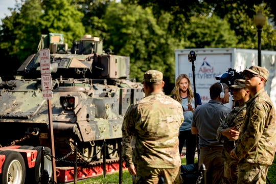A reporter speaks on camera next to one of two Bradley Fighting Vehicles parked nearby the Lincoln Memorial for President Donald Trump's 'Salute to America' event honoring service branches on Independence Day.