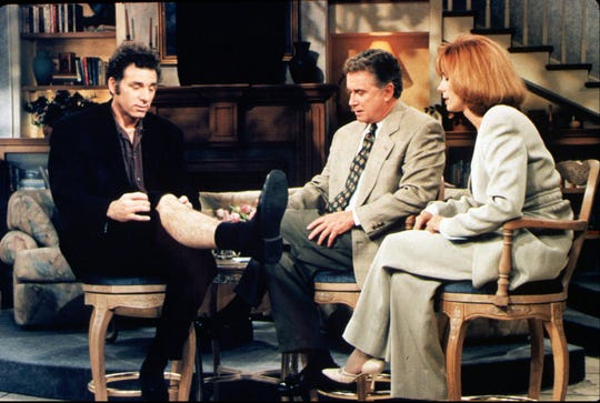 """Kramer (Michael Richards) shows some leg during a talk-show appearance with Regis Philbin and Kathie Lee Gifford to promote his coffee-table book about coffee tables on """"Seinfeld."""""""
