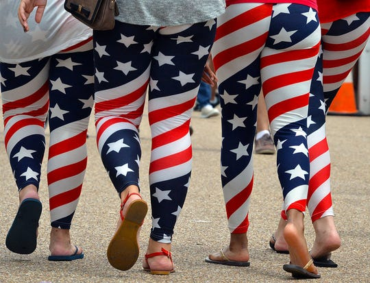 Four young women wear US flag leggings marking the Independence Day as they walk on Pennsylvania Avenue in Washington, DC on July 4, 2015.