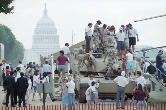 Tourists swarm over an M-1 tank on the Mall near the Capitol on Friday, June 7, 1991 in Washington. The tank and other weapons will be a part of the Desert Shield and Desert Storm Victory Celebration in Washington on Saturday. (AP Photo/Ron Edmonds)