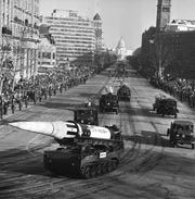 An Army Pershing missile mounted on a tank-like carrier catches the sunlight as the inaugural parade for President John F. Kennedy draws attention of spectators along Pennsylvania Avenue in Washington, Jan. 20, 1961. Other missiles, from front, are: Lacrosse, Nike Hercules and Nike Zeus. This view toward the Capitol was made from a stand at the Treasury Department. (AP Photo)