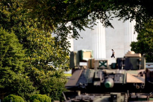 A woman walks along the columns of the Lincoln Memorial as one of two Bradley Fighting Vehicles is parked nearby for President Donald Trump's 'Salute to America' event honoring service branches on Independence Day.