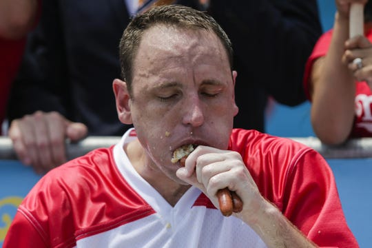 Joey Chestnut competes in the annual Nathan's Hot Dog Eating Contest on July 4, 2018 and set the by eating 74 hot dogs and buns in 10 minutes.