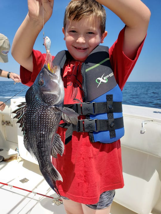 Mason Murdoch, 6 of Howell, with a sea bass he caught on his dad's boat.