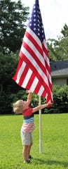 Brody Biggs, 4, salutes the flag his way after Thursday morning's River Oaks Neighborhood Parade in Abilene.