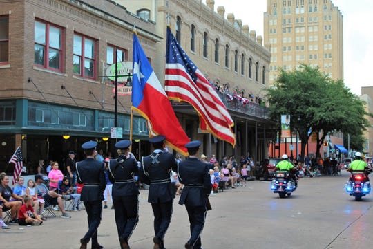 Parade-goers line the sidewalks and balconies Wednesday evening on Cypress Street to cheer the colors as the second Stars & Stripes Parade begins. A good breeze unfurled the flags.