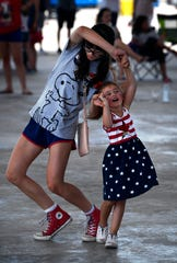 Kelly Johnson, 13, spins Kynslee Bovino, 3, during a musical performance at the Taylor County Expo Center on Thursday at the second Freedom Festival.