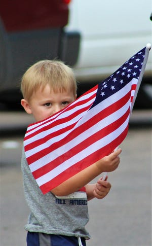 Jordan Hendley, 3, of Albany waves his flag along the Stars & Stripes Parade route Wednesday in downtown Abilene.