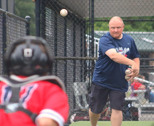 Kitsap Rebels coach Ryan Parker throws pitches to 15-and-under catcher Caleb Guadamuz during the team's game July 3 at Sehmel Homestead Park in Gig Harbor.