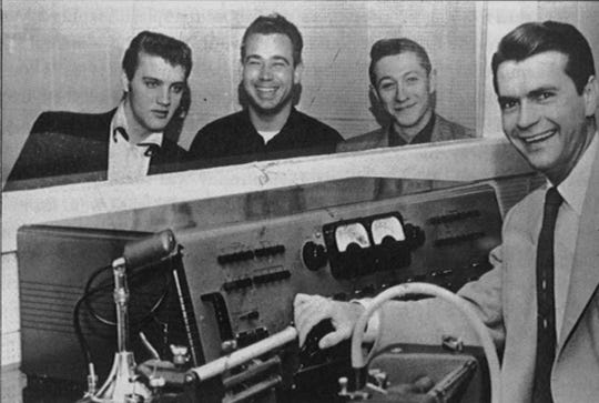 "Elvis Presley, left, with bass player Bill Black, second left, guitarist Scotty Moore and Sun Records and Memphis Recording studio head Sam Phillips, right, are shown at an early recording session in Memphis in 1954. On July 5, 1954, Presley cut ""That's All Right"" in Sun Studio, backed by Moore and Black. It was his first commercial recording."