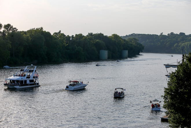 Boats move up and down the Cumberland River before the fireworks show at McGregor Park in Clarksville, Tenn., on Wednesday, July 3, 2019.