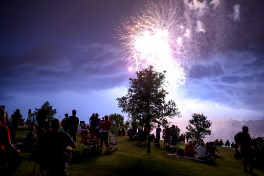 Fireworks explode at the same time as lighting strikes in the plane ahead at Liberty Park and Marina in Clarksville, Tenn., on Wednesday, July 3, 2019.