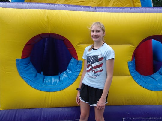 Rebekah Unkefer poses by an inflatable in the kids' area Wednesday during the Freedom Celebration at the Coshocton County Fairgrounds.