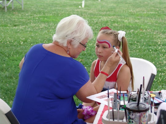 Annabelle Rummell celebrates at the Freedom Fest by getting her face painted with patriotic colors Wednesday evening. at the Coshocton County Fairgrounds.