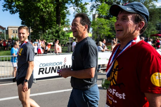 Montana Gov. Steve Bullock gets a finisher medal after running in a July 4 road race in downtown Cedar Rapids, Iowa. Some are criticizing the governor for being away too much from the state for his presidential campaign.