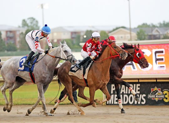 The horses race through the rain during the Prairie Meadows Annual All-American Extravaganza celebration on Wednesday, July 3, 2019, with live horse racing, live music outdoors with the band SPAM, and a fireworks show at dusk.