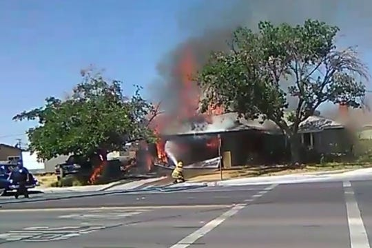 A firefighter works to extinguish a fire, Thursday following an earthquake in Ridgecrest, Calif. Emergency crews were also dealing with small vegetation fires, gas leaks and reports of cracked roads.