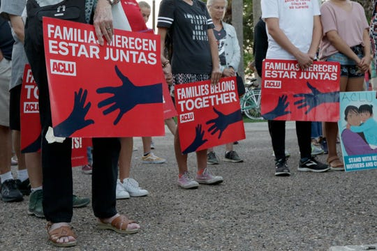 """People hold signs that read """"families belong together"""" in English and Spanish during a vigil June 30 at Alice Hope Wilson Park in Brownsville, Texas, to advocate against the separation of migrant families at the U.S.-Mexico border."""