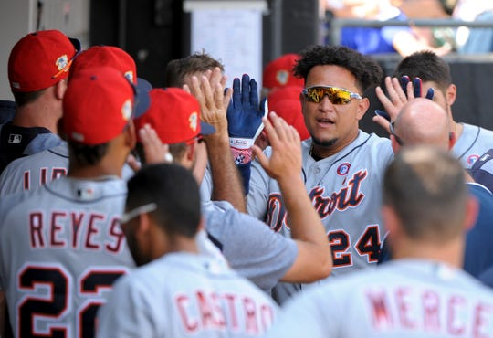 The Detroit Tigers' Miguel Cabrera gets welcomed into the dugout after his home run in the seventh inning.