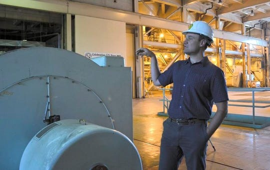 Marquette Board of Light and Power Executive Director Tom Carpenter stands inside the Shiras Steam Plant while telling tour attendees about the plant's rich history June 19 in Marquette.