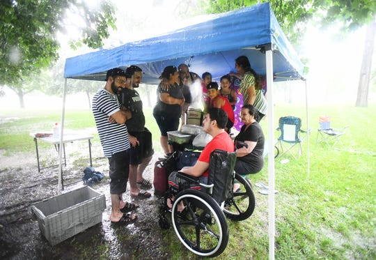 Members of the Ghazala family aren't budging despite a heavy rain fall that went through Clawson on Thursday afternoon during the annual Fourth of July festival.