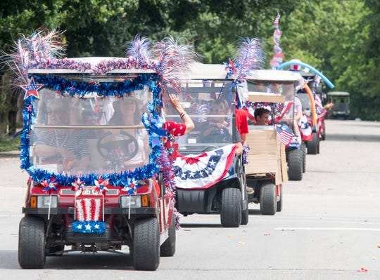 Golf carts decorated in patriotic flair roll down Main Street in New Harmony, Ind. during their Independence Day Celebration Thursday, July 4, 2019.