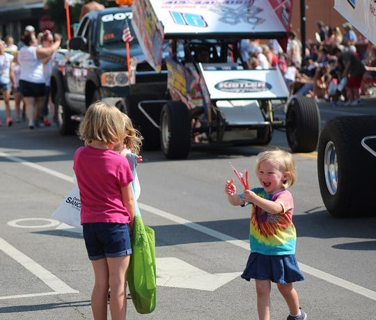 Kendra Paeth of Gibsonburg brings a handful of candy passed out at the annual Fourth of July parade.