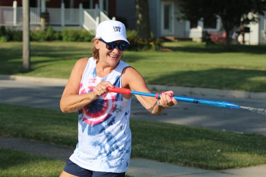 Sue Benedict takes time out of her 5K race at the Star Spangled Squirt Gun Run to douse her family with a waiting squirt gun.