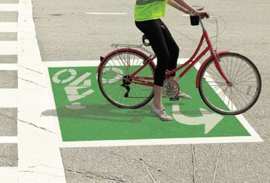 Graphic showing how the green bicycle turning boxes to will appear at the intersection of Daniels Parkway and Treeline Avenue.  It will be first deployment of the green turn box. The motorist pictured had come across the road on the sidewalk to the left and turned her bicycle to be ready to complete a left turn when the light turns green.