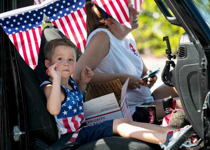 Cash Corbitt, 4, thows candy while riding with the Caloosa Jeepers in the Fort Myers Beach Fourth of July Parade on Thursday, July 4, 2019.