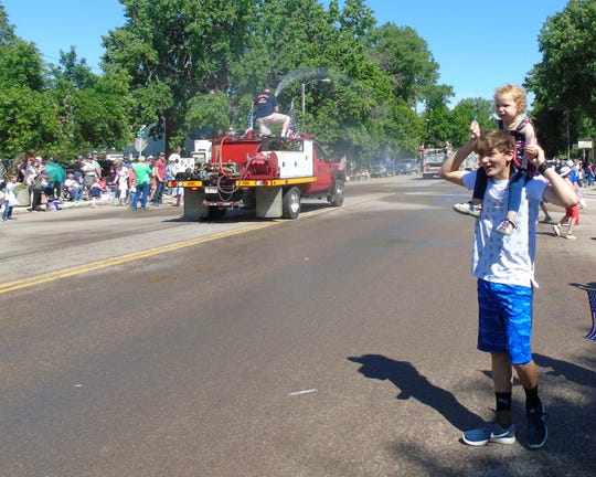 A DNRC fire truck sprays the crowd as the Choteau 4th of July parade rolls down Main Street on Thursday.