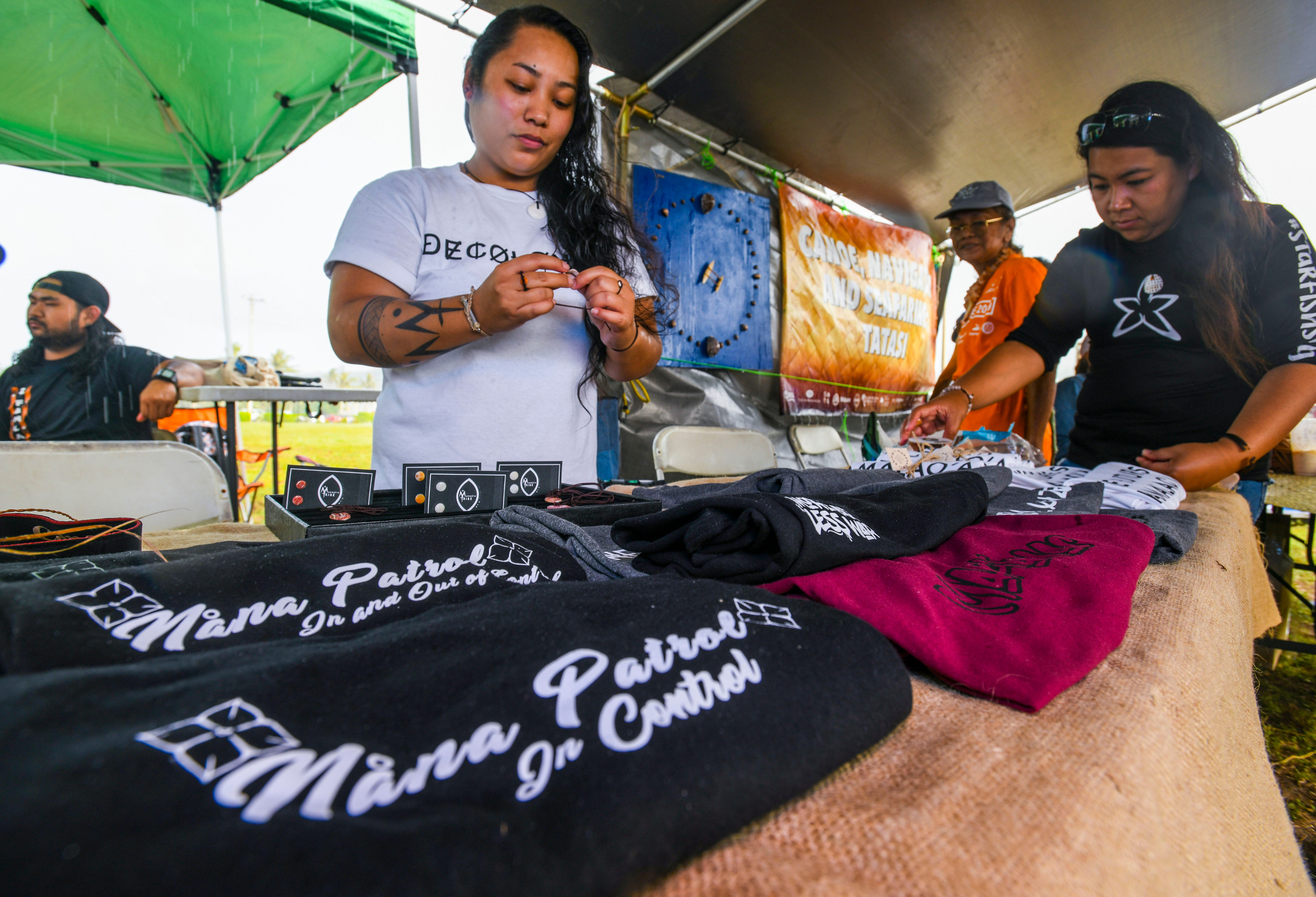 Makmåta' Tribe owner Kaiana San Nicolas puts together a shell necklace to sell during the Na'lå'la': Songs of Freedom, Vol. 3 concert at Adelup in this July 4, 2019, file photo. The government of Guam continues to explore its options to salvage a political status plebiscite.