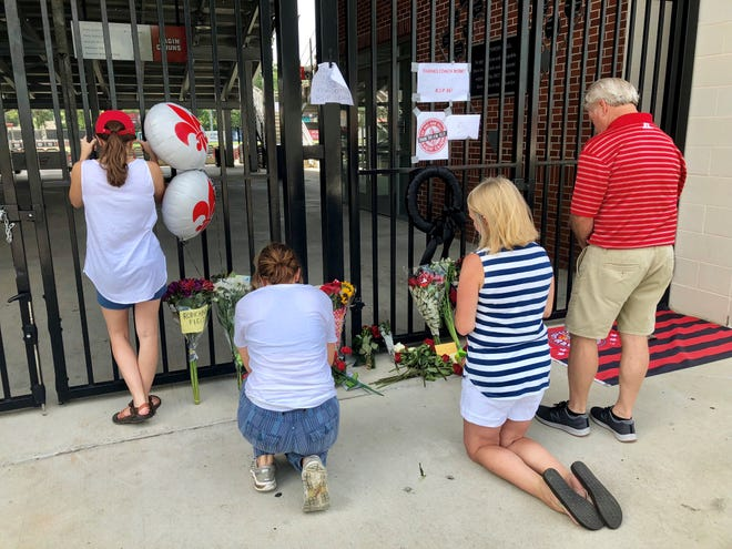 """People pray and place flowers and notes at M.L. """"Tigue"""" Moore Field at Russo Park on Thursday, July 4, a day after learning of the death of legendary University of Louisiana at Lafayette baseball Coach Tony """"Robe"""" Robichaux."""
