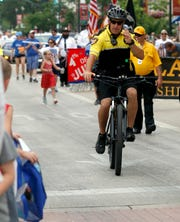 Fairfield County Sheriff's Deputy T.J. Strawn waves to the crowd as he and other members of the department's newly revived bicycle unit ride in the Lancaster-Fairfield County Fourth of July Parade, Thursday, July 4, 2019, in downtown Lancaster.