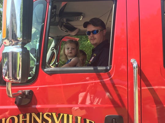 Peyton Snavely sits in a Johnsville fire truck with her uncle, firefighter Nathan Bell, at the Pastoral in the Park celebration in Lexington.
