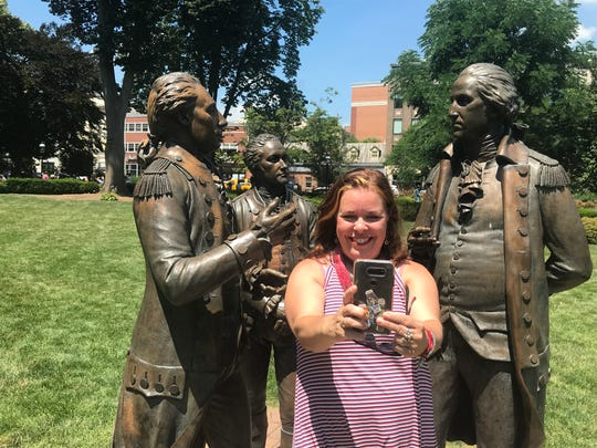 The seventh annual Revolutionary Times   event began with costumed re-enactors, live music and a reading of the Declaration of Independence on the Morristown Green. Cynthia Miller of Princeton takes a selfie with the Green's satue of George Washington, Alexander Hamilton and the Marquis de Lafayette. July 4, 2019.