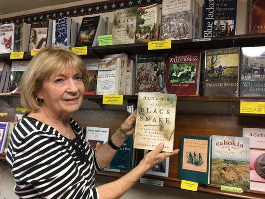 Nancy Knapke, director, holds a book she recommends in the gift shop at Fort Recoverty State Museum.