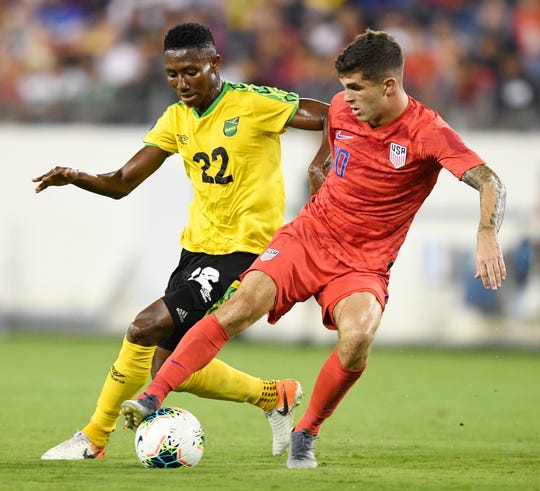Jamaica midfielder Devon Williams (22) and United States midfielder Christian Pulisic (10) battle for the ball during the second half of a Concacaf Gold Cup Semifinal game at Nissan Stadium in Nashville, Tenn., Wednesday, July 3, 2019.