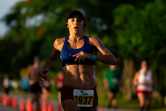 Cape Coral's Kathryn Repperger crosses the finish line taking first in the women's division on Thursday during the annual Moe's Firecracker 5k race in Naples.