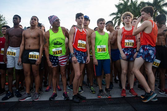 Saindeley Dorsainvil, from left, Jeimy Rosales, Richard Villapando, Kolton Pickard, Max Arjani, Avery Geerlings and Payton Arabie, step up to the starting line before the start of the annual Moe's Firecracker 5k race on Thursday in Naples.