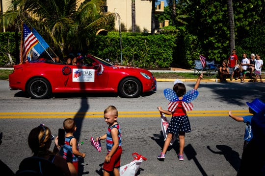 Parade watchers wave as the Daughters of the American Revolution drive down the street during the Fourth of July parade in downtown Naples on Thursday, July 4, 2019. Many groups in the community were represented with floats, cars, and other vehicles.