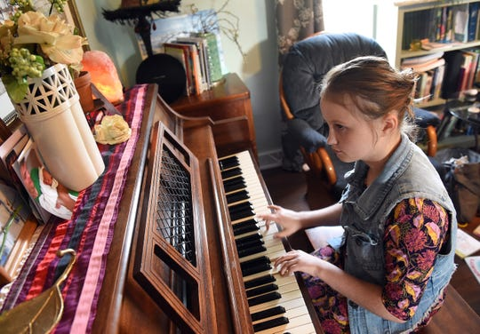 Perseus Decker, 13, plays piano in her Newark home. Decker, who plays many instruments, first started playing piano when she was 2 years-old. She frequently performs at her family's church, Church of God at God's Acres, and hopes to be able to join the the Ohio State School for the Blind's marching band.