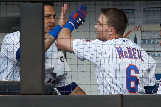 New York Mets catcher Wilson Ramos, left, congratulates Jeff McNeil in the dugout after McNeil hit a solo home run during the first inning of the team's game against the New York Yankees, Wednesday, July 3, 2019, in New York.