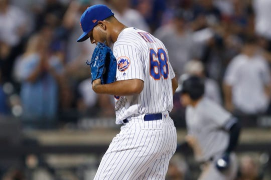 New York Mets relief pitcher Wilmer Font looks down after allowing a solo home run to New York Yankees Gio Urshela, rear, during the sixth inning of a baseball game Wednesday, July 3, 2019, in New York.