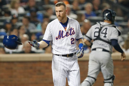 New York Mets' Todd Frazier (21) tosses his batting helmet after he struck out looking as New York Yankees catcher Gary Sanchez (24) heads to the dugout during the sixth inning of a baseball game Wednesday, July 3, 2019, in New York.