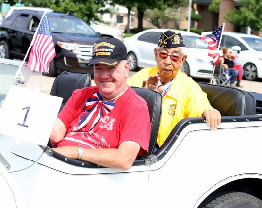 Decorated Korean War veteran Ruben Acosta, right, rode in this year's parade as grand marshal.