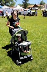 Anissa Powers, of Farmington, pushes her son William in a stroller during the July 4 Party in the Park at Brookside Park in Farmington.