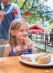 Zoe Hall, 6, of Milton, manages a smile Wednesday while stuffing her mouth during the Sertoma hot dog eating contest in Seville Square in downtown Pensacola.