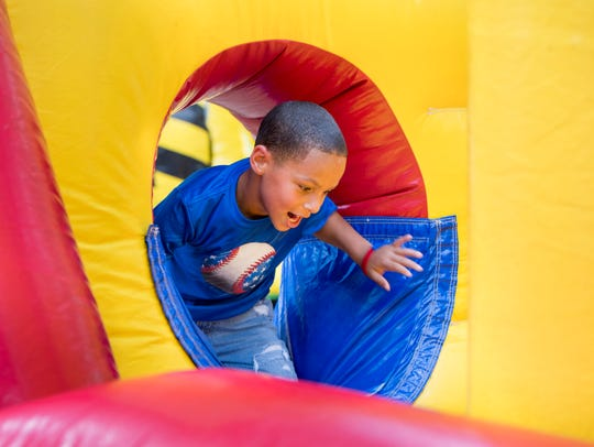 Ja'Kobi Whitaker, 6, of Idabel, Oklahoma, makes his way through an inflatable obstacle course during the Sertoma's annual Fourth of July Celebration in Seville Square in downtown Pensacola.