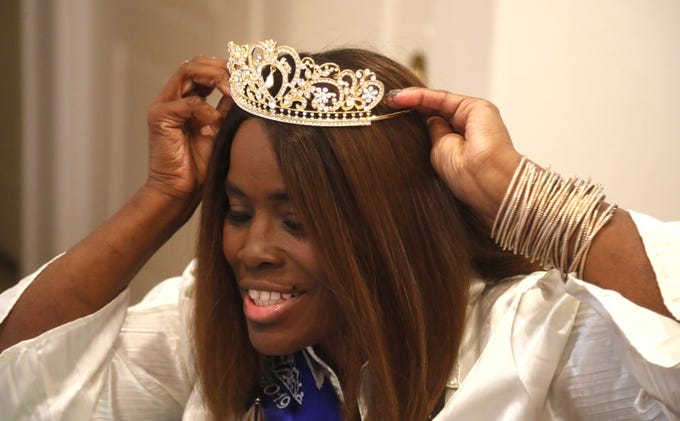Shawnique Cotton, Ms. Wheelchair Arizona, tries on her crown in her home in Mesa, Ariz. on June 30, 2019.